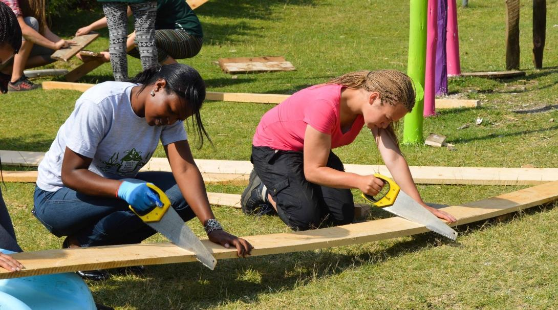 Two women work together to saw wood to build playground equipment during their volunteer building work abroad.